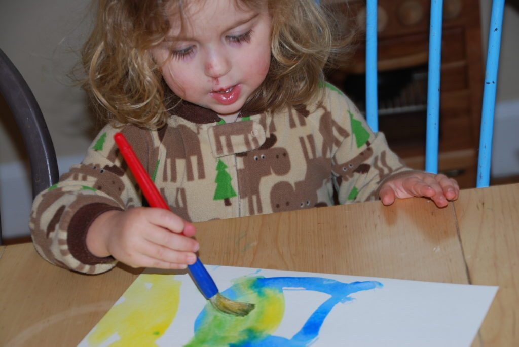3 year old working on painting for homemade watercolor alphabet chart